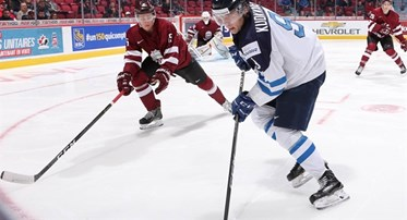 MONTREAL, CANADA - JANUARY 2: Finland's Janne Kuokkanen #9 plays the puck while Latvia's Tomass Zeile #15 defends during relegation round action at the 2017 IIHF World Junior Championship. (Photo by Andre Ringuette/HHOF-IIHF Images)